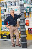 Full length portrait of confident senior man standing by stacked toolboxes in hardware shop