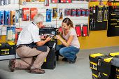 Full length of senior salesman showing tools to female customer in hardware shop