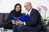 pic of hijabs  - Senior Businessman working with Arabian Businesswoman wearing hijab - JPG