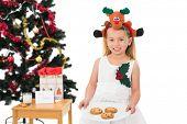 Festive little girl holding fresh cookies on white background