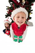 Festive little siblings smiling at camera holding gifts on white background