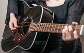 Female hand playing acoustic guitar.guitar