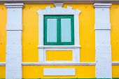 A green window with yellow wall