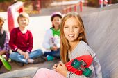 Close up view of blond girl with skateboard