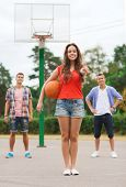 summer vacation, holidays, games, gesture and people concept - group of smiling teenagers playing basketball and showing thumbs up outdoors