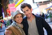 Couple standing in Time Square quarter by night