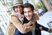Man giving piggyback ride to girlfriend, having fun