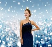 people, holidays, royalty and christmas concept - smiling woman in evening dress wearing golden crown over snowy city background