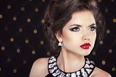 Beautiful Brunette Woman Model With Makeup And Hairstyle, Necklace, Fashion Earrings Over Bokeh Ligh