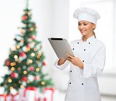 cooking, holidays, technology and people concept - smiling female chef, cook or baker with tablet pc computer over living room with christmas tree background