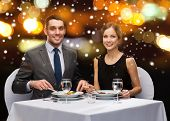 food, christmas, holidays and people concept - smiling couple eating main course at restaurant over night lights background