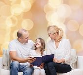 family, childhood, holidays and people - smiling mother, father and little girl reading book over beige lights background