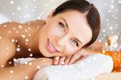 beauty, health, people and spa concept - beautiful young woman with body oil in spa