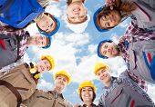 image of huddle  - Directly below portrait of multiethnic architects standing in huddle against sky - JPG