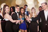 Happy Friends Toasting Drinks At Nightclub