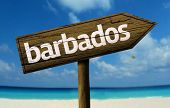 Barbados wooden sign with a beach on background