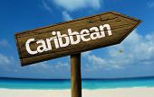Caribbean wooden sign with a beach on background