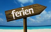 Ferien wooden sign with a beach on background