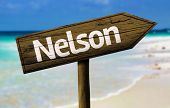 Nelson, New Zealand wooden sign with a beach on background