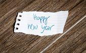 stock photo of reveillon  - Happy New Year written on piece of paper - JPG