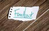 Feedback written on the paper on a wood background
