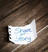 Share your story written on the paper on a wood background