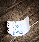 Social Media written on the paper on a wood background