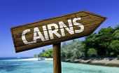 Cairns, Queensland, Australia wooden sign with a beach on background