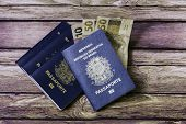 stock photo of brazilian money  - New Brazilian Passport and some brazilian money on the wooden table - JPG