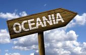 Oceania wooden sign with clouds as the background