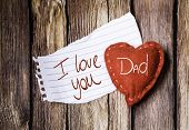 I Love You Dad written on a peace of paper and a heart on a wooden background
