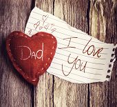 Dad I Love You written on a peace of paper and a heart on a wooden background