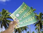 Hand holds a homemade soccer tickets on a beautiful day with many palm trees