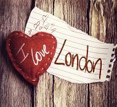 I Love London written on a peace of paper and a heart on a wooden background