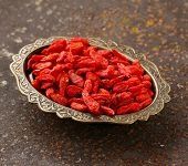 red goji berries on a old iron background