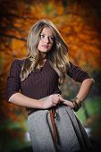 Beautiful elegant woman standing in a park in autumn.Young pretty woman at the autumn park