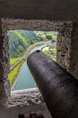 An Old Cannon And A View Through The Castle's Window
