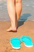 Woman Goes Barefoot On The Sand To The Water