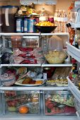 stock photo of refrigerator  - An open refrigerator door showing a full stocked fridge loaded up with food and fresh ingredients - JPG
