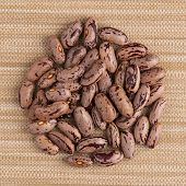 pic of pinto bean  - Top view of circle of pinto beans against brown vinyl background.