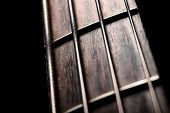 stock photo of fret  - Detail of the fret board of a bass guitar on a dark background.