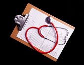 foto of medical chart  - Medical Chart and stethoscope isolated on black background - JPG