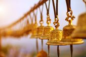 stock photo of nepali  - Nepaly traditional Bells over the sun at sunset - JPG