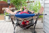 pic of recliner  - Father and daughter relaxing together on the patio both lying on a two - JPG