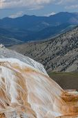 stock photo of mammoth  - The amazing Mammoth Hot Springs in Yellowstone National Park with steam rising from the colorful staircase formation distant high mountains and a fluffy cloud sky - JPG