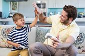 image of indoor games  - Father and son playing video games together at home in the living room - JPG