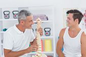 image of herniated disc  - Doctor showing anatomical spine to his patient in medical office - JPG