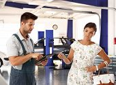 picture of disgusting  - Elegant young woman with disgust on face handing car key to car mechanic - JPG
