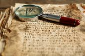 stock photo of hieroglyph  - Grunge papers with hieroglyphics with magnifier close up - JPG