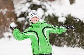 pic of snowball-fight  - Young boy throwing snowballs during a winter snow fight smiling with glee as he takes aim in a winter landscape - JPG